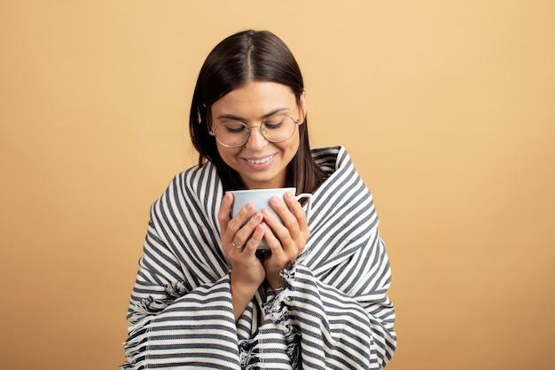 Jonge vrouw het drinken koffie die in een deken wordt verpakt. jonge vrouw voelt zich comfortabel