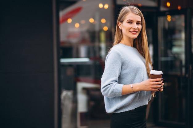 Jonge vrouw het drinken koffie door de koffie