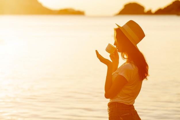 Jonge vrouw het drinken koffie op zonsondergang
