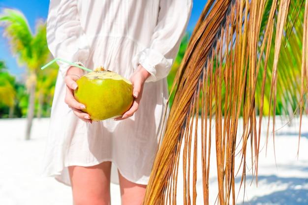 Jonge vrouw het drinken kokosmelk op hete dag op het strand. close-upkokosnoot in vrouwelijke handen