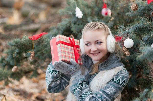 Jonge vrouw het drinken stempel op kerstmismarkt.