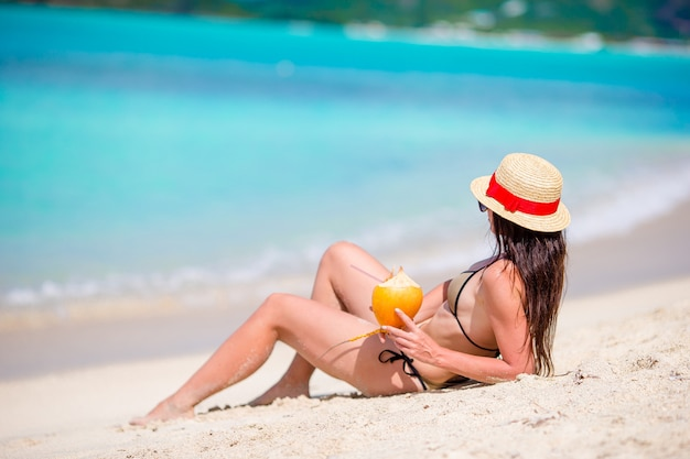Jonge vrouw het drinken van kokosmelk op warme dag op het strand.