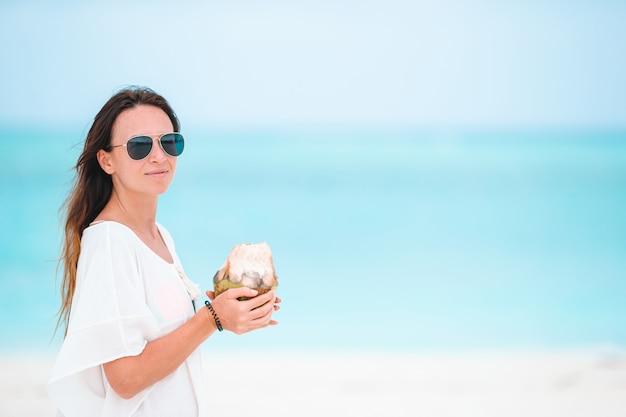 Jonge vrouw het drinken van kokosmelk tijdens tropische vakantie