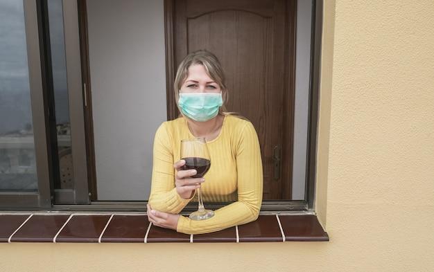 Jonge vrouw het drinken van wijn die thuis bij het venster leunt