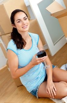 Jonge vrouw het drinken wijn na het uitpakken van karton