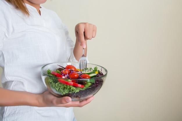 Jonge vrouw het eten van gezonde salade
