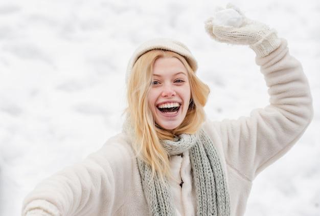 Jonge vrouw het gooien van een sneeuwbal buiten