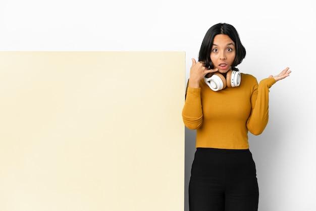 Jonge vrouw het luisteren muziek met een groot leeg aanplakbiljet over geïsoleerde muur die telefoongebaar en twijfelen maakt