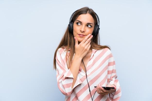 Jonge vrouw het luisteren muziek met mobiel denkend een idee
