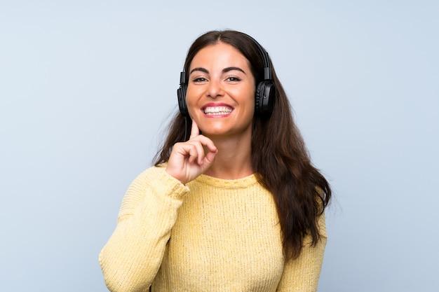 Jonge vrouw het luisteren muziek met mobiel over geïsoleerde blauwe muur