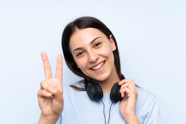 Jonge vrouw het luisteren muziek over geïsoleerde blauwe muur