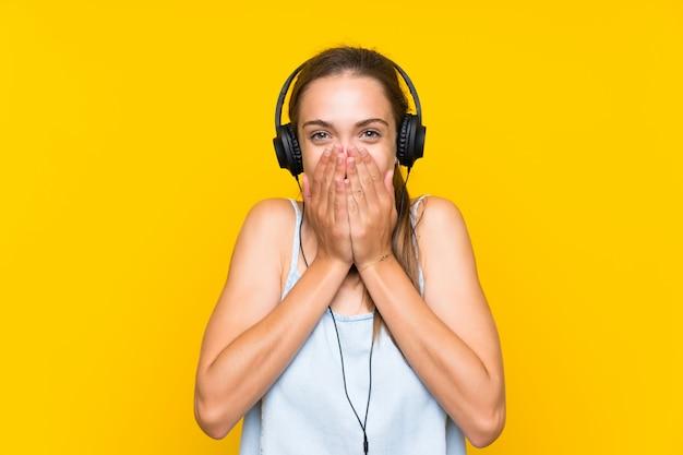 Jonge vrouw het luisteren muziek over geïsoleerde gele muur met verrassingsgelaatsuitdrukking