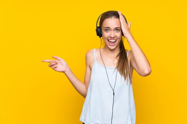 Jonge vrouw het luisteren muziek over geïsoleerde gele muur verrast en wijzende vinger aan de kant