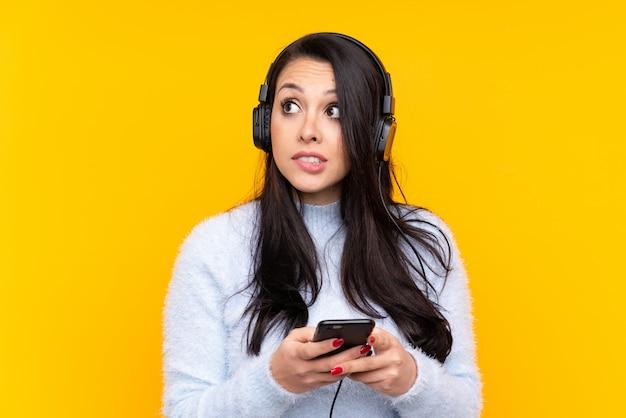 Jonge vrouw het luisteren muziek over geïsoleerde muur