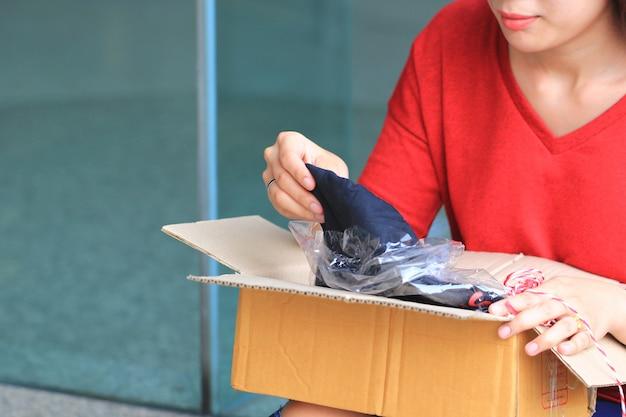 Jonge vrouw het openen doos met pakket thuis, het verschepen en post de dienstconcept