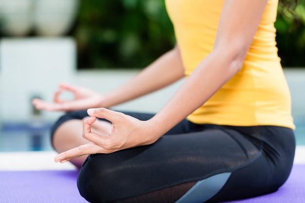 Jonge vrouw het praktizeren yoga in lotusbloempositie in openlucht