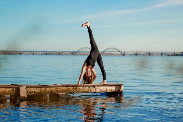 Jonge vrouw het praktizeren yogaoefening bij stille houten pijler met stadsachtergrond. sport en recreatie in de stad