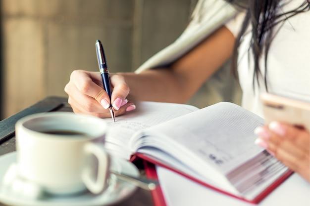 Jonge vrouw het rechtse schrijven plannen op kleine agenda in koffie dicht omhoog