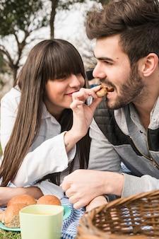Jonge vrouw het voeden koekjes aan haar vriend bij picknick