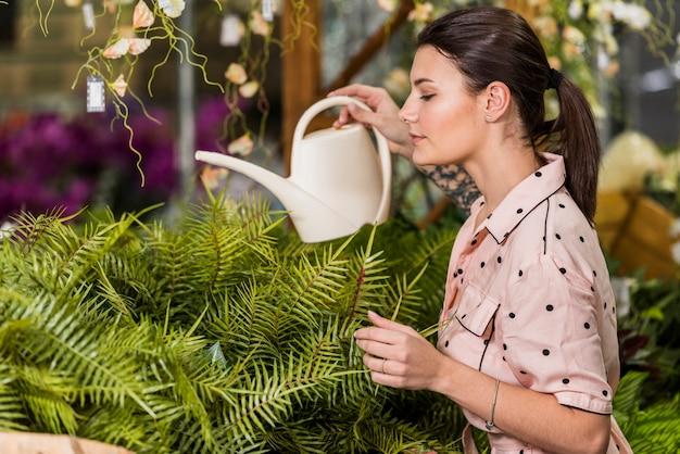 Jonge vrouw het water geven installatie in groen huis