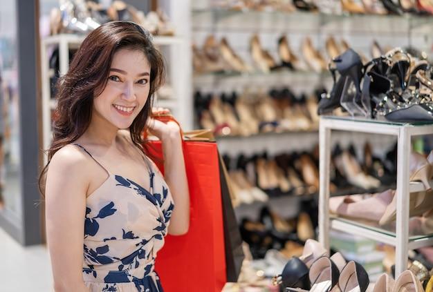 Jonge vrouw het winkelen schoenen in winkel