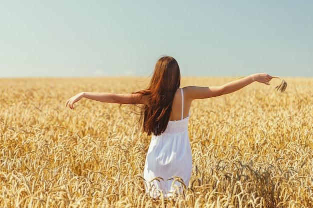Jonge vrouw hief haar handen in de stralen van zonlicht op de achtergrond van een veld met rijpe tarwe