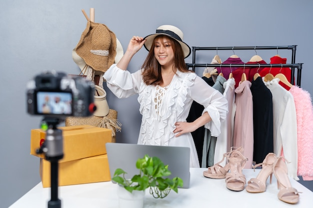 Jonge vrouw hoed en kleding online verkopen via camera live streaming, zakelijke online e-commerce thuis