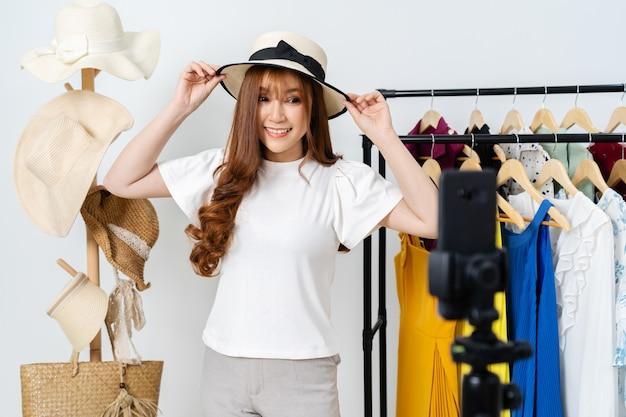 Jonge vrouw hoed en kleding online verkopen via smartphone live streaming, zakelijke online e-commerce thuis