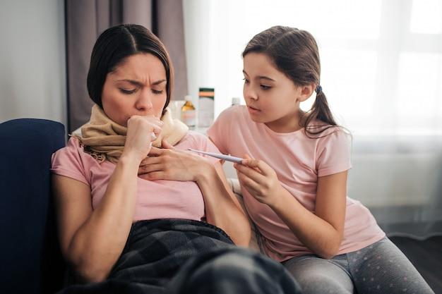 Jonge vrouw hoesten. ze bedekte mond met vuist. brunette zit op de bank samen met haar dochter in de kamer. ze kijkt naar de thermometer in de handen van het kind. meisje omhelst moeder.