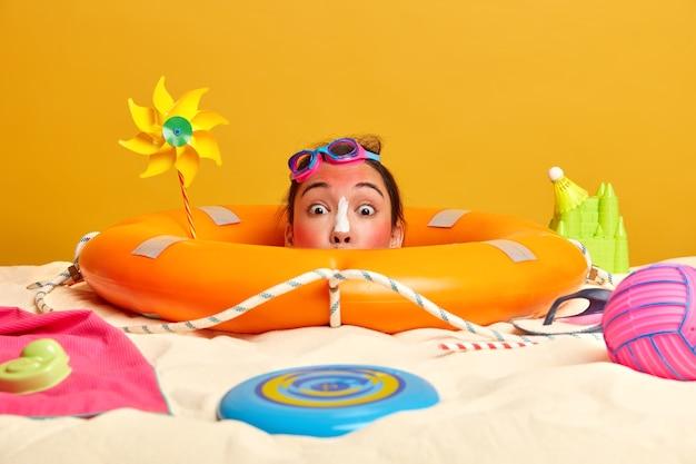Jonge vrouw hoofd met zonnebrandcrème op gezicht omgeven door strandaccessoires