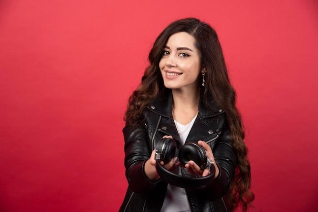 Jonge vrouw hoofdtelefoon geven en poseren op een rode achtergrond. hoge kwaliteit foto