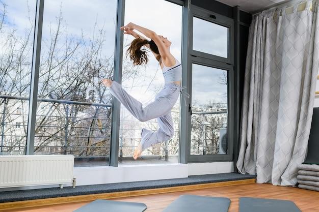 Jonge vrouw hoog blootsvoets springen in lichte studio hal, gezellige grijze broek en top, gezonde, actieve levensstijl dragen