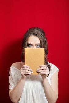 Jonge vrouw houdt blanco boek in lederen omslag op de achtergrond van rode gordijnen