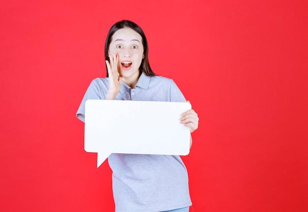 Jonge vrouw houdt bord vast en lacht