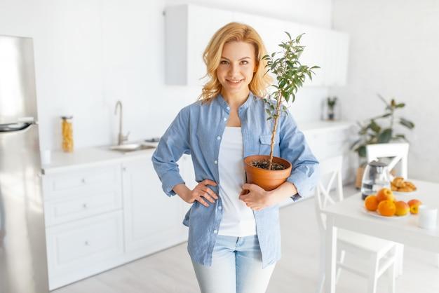 Jonge vrouw houdt een bloem in een pot op de keuken met sneeuwwit interieur.