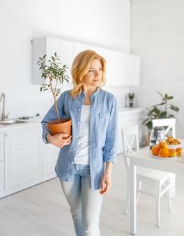 Jonge vrouw houdt een bloem in een pot op de keuken