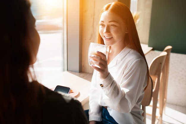 Jonge vrouw houdt een kopje koffie en spreekt met haar vriend. vrouwelijk model drinkt koffie en zit in een café