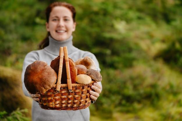 Jonge vrouw houdt een mand vast in een grijze trui vol herfstoogst van boletuspaddestoelen