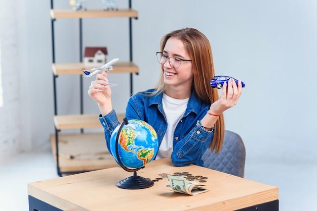 Jonge vrouw houdt een model van vliegtuig en auto en kiest voor beter vervoer voor reizen. reis- en vakantie concept.