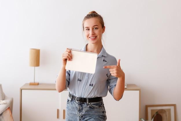 Jonge vrouw houdt een witte blocnote en toont het