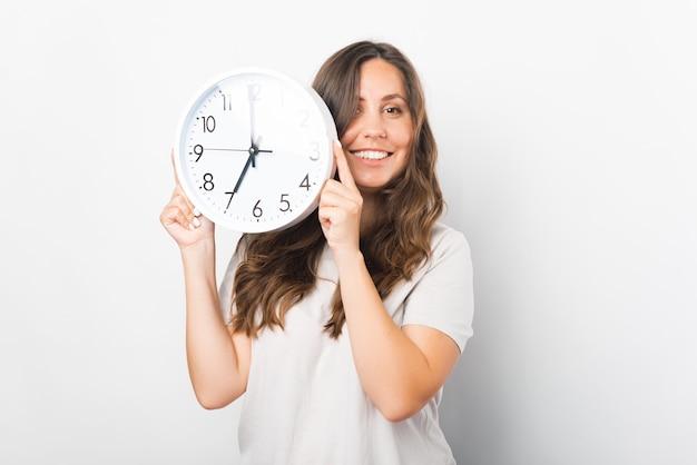 Jonge vrouw houdt een witte klok in een studio.