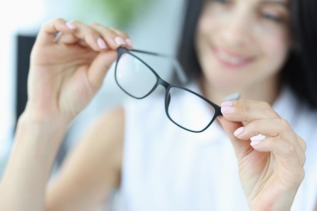 Jonge vrouw houdt een zwarte bril vast voor zicht in handen