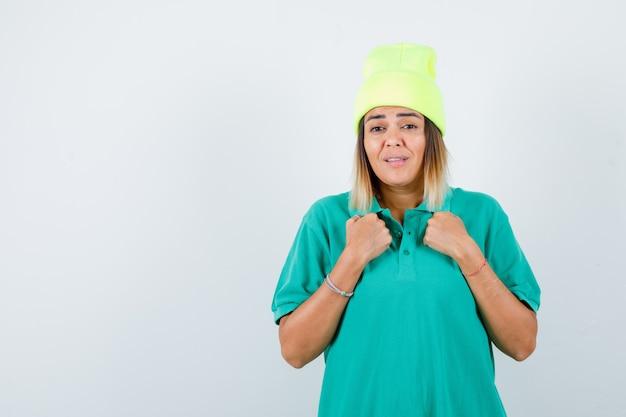 Jonge vrouw houdt gebalde vuisten op de borst in polo t-shirt, beanie en ziet er chagrijnig uit, vooraanzicht.