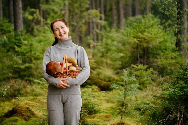 Jonge vrouw houdt gelukkig een rieten mand met eetbare paddenstoelen vast tegen de achtergrond van bos
