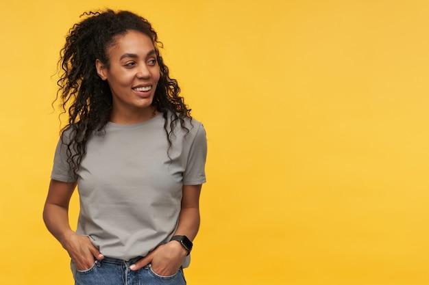 Jonge vrouw houdt haar handen in de zak, voelt zich gelukkig en tevreden kijkt opzij op geel