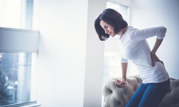 Jonge vrouw houdt haar onderrug vast terwijl ze aan ernstige rugpijn lijdt.