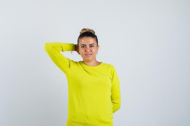 Jonge vrouw houdt hand achter hoofd in trui en ziet er charmant uit