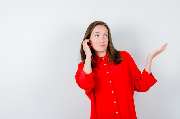 Jonge vrouw houdt hand in de buurt van oor, spreidt handpalm opzij in rode blouse en kijkt gefocust. vooraanzicht.