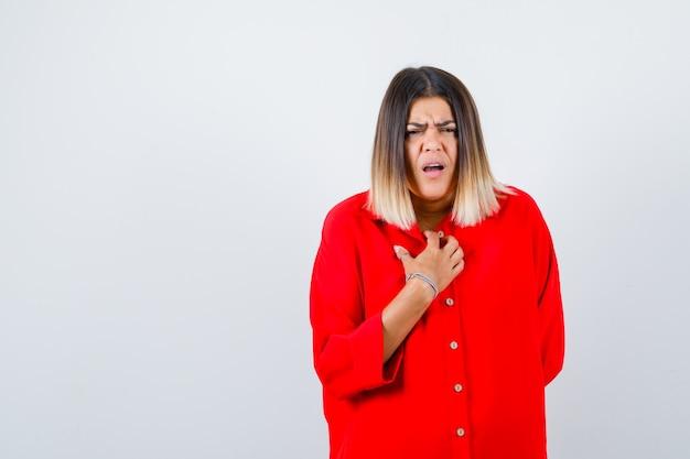 Jonge vrouw houdt hand op borst in rood oversized shirt en kijkt aarzelend. vooraanzicht.