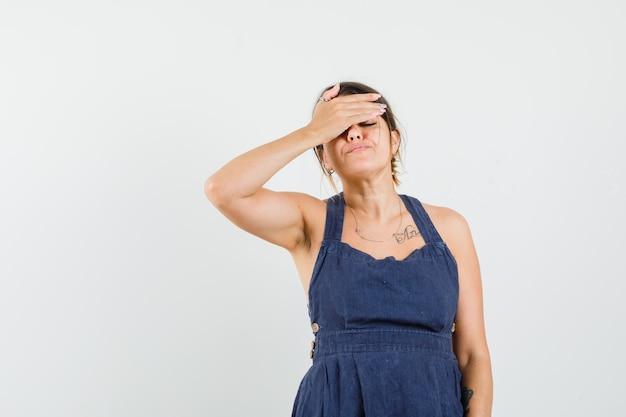 Jonge vrouw houdt hand op ogen in donkerblauwe jurk en ziet er vergeetachtig uit forget